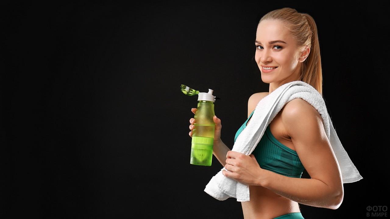 Девушка с бутылкой воды и полотенцем