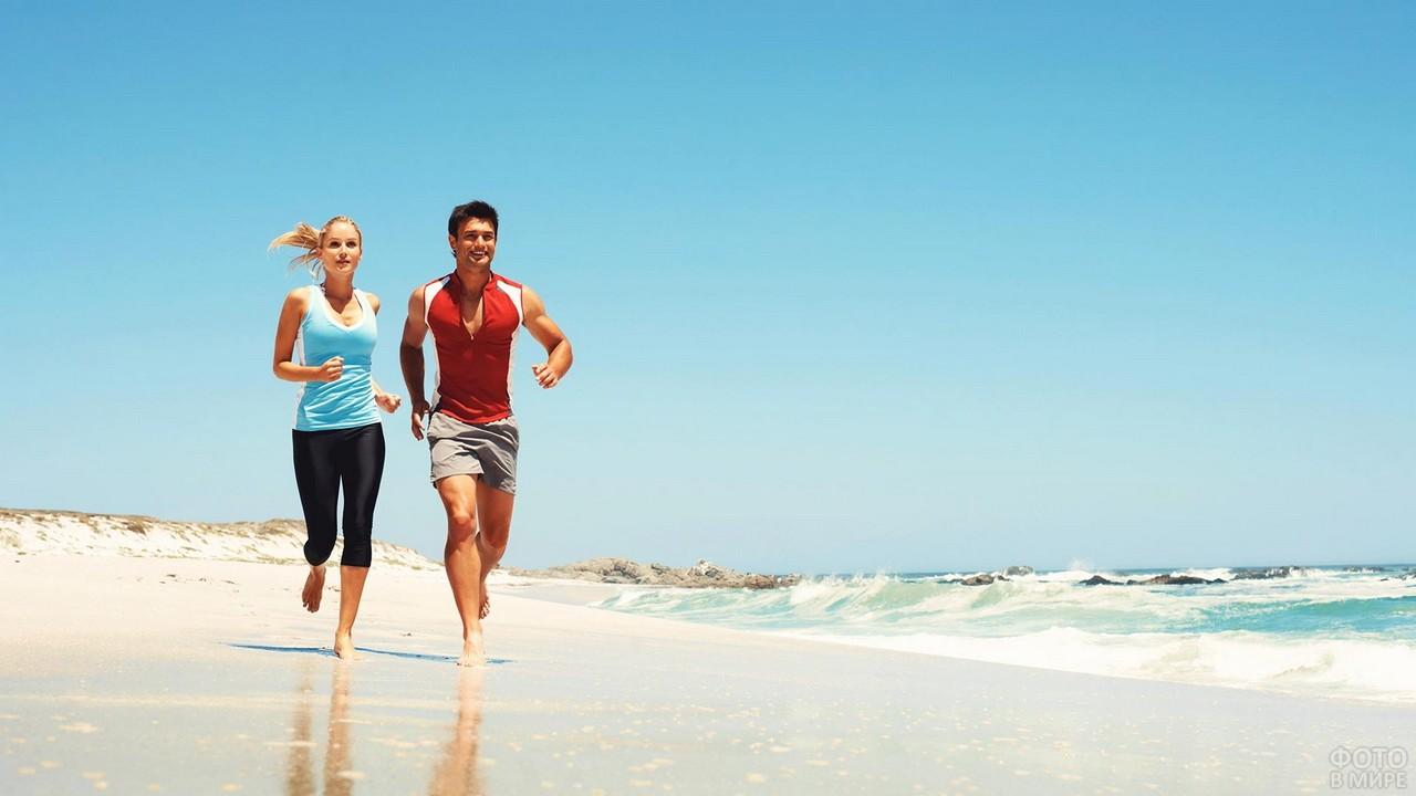 Девушка с парнем бегут вдоль берега