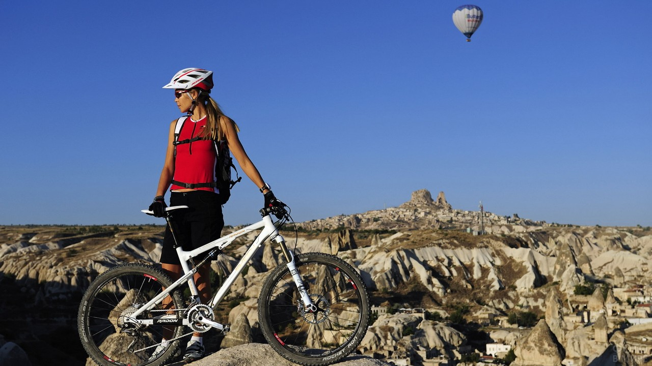 Девушка с велосипедом на вершине горы