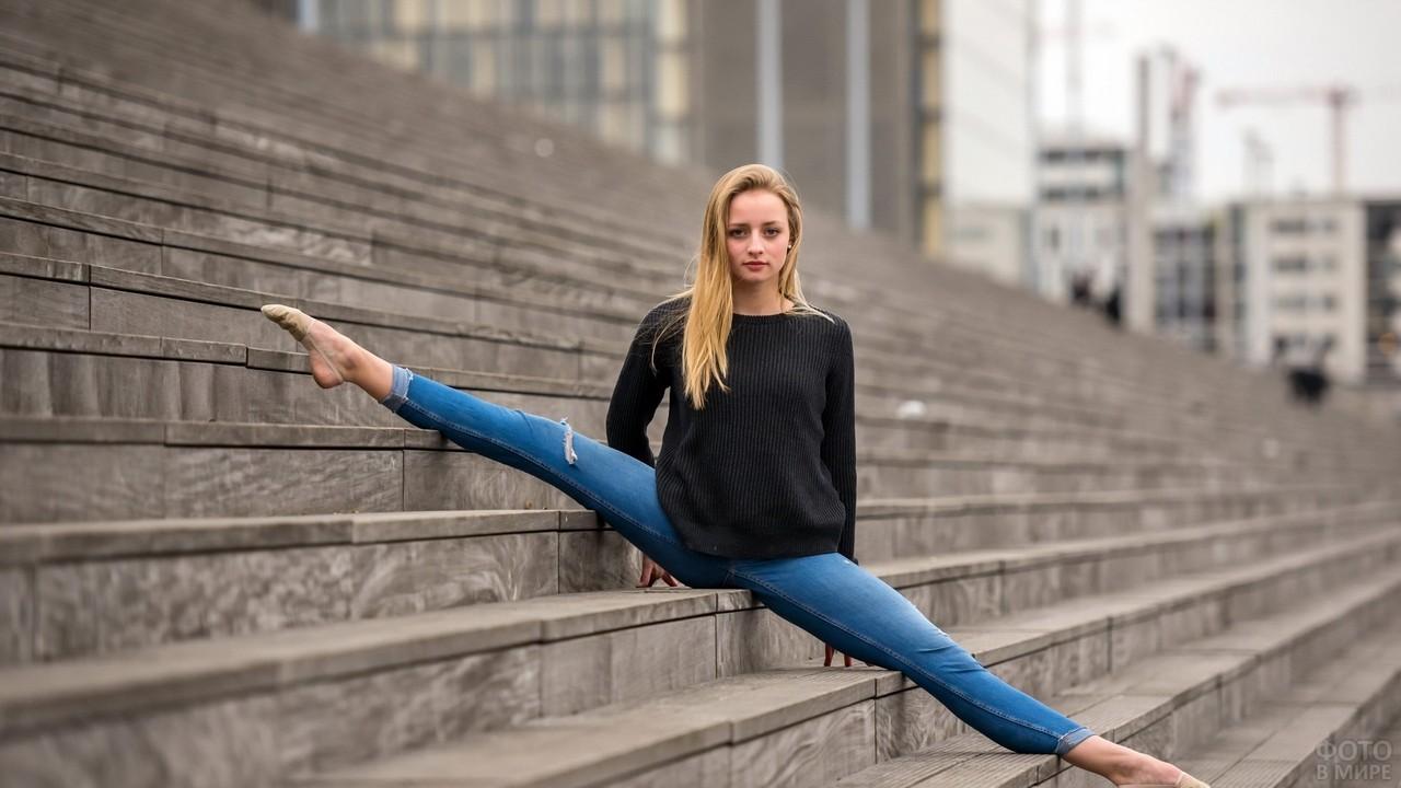 Девушка сидит на шпагате на лестнице