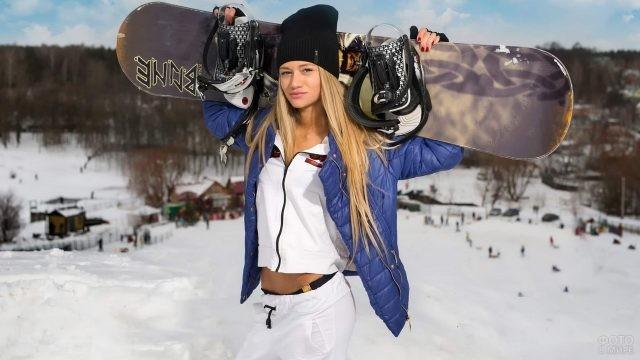 Девушка со сноубордом на склоне