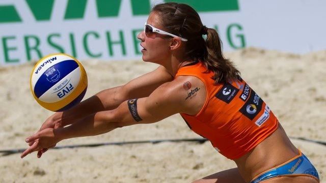 Девушка в солнцезащитных очках играет в волейбол
