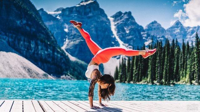Девушка выполняет стойку на руках у озера