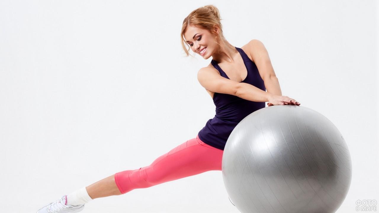 Девушка занимается фитнесом с мячом