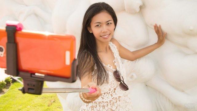 Азиатка фотографируется оранжевым телефоном