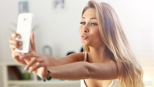 Блондинка фотографируется на белый телефон