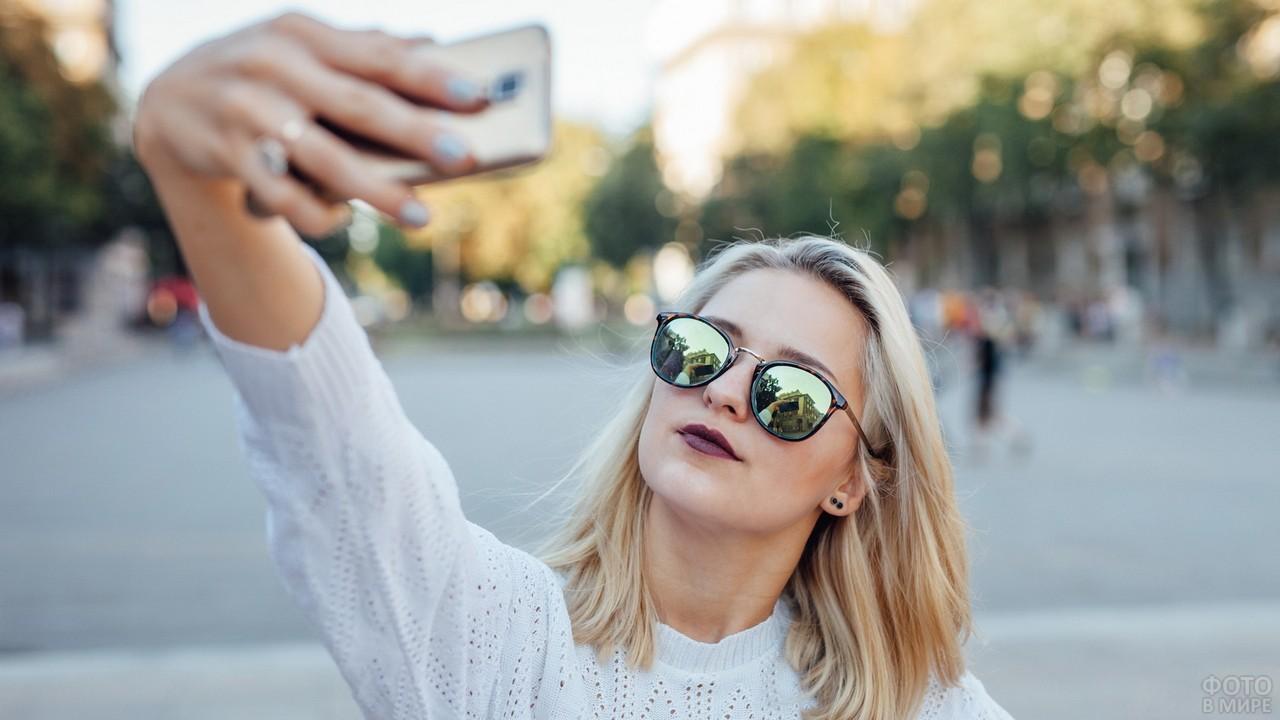 Блондинка фотографируется в солнцезащитных очках