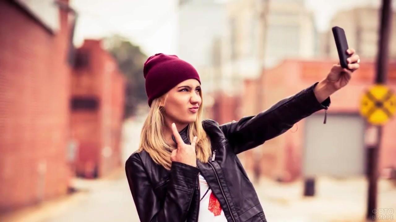 Блондинка в шапке делает фото на телефон
