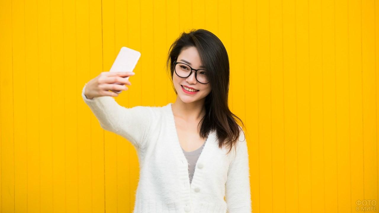 Брюнетка с телефоном на фоне жёлтой стены