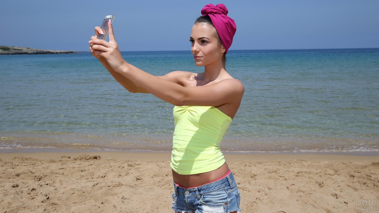 Девушка делает фото на берегу моря