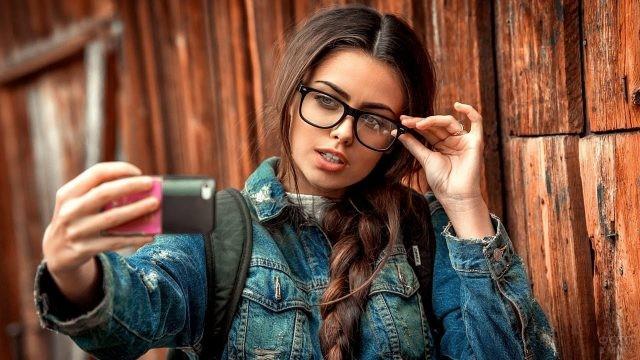 Девушка фотографируется, держась рукой за очки
