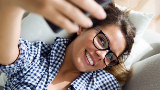 Девушка в очках снимает себя на телефон