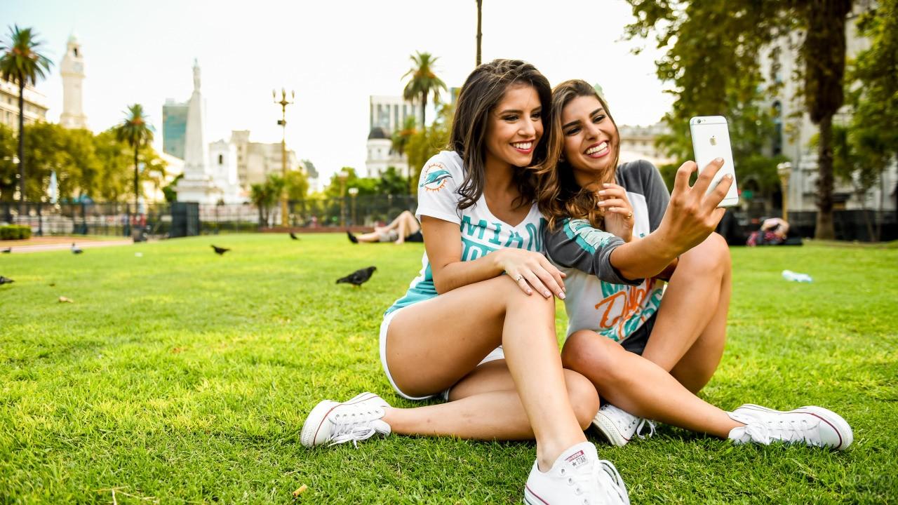 Девушки делают селфи сидя на газоне
