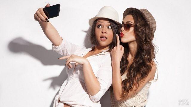 Две девушки фотографируются на телефон