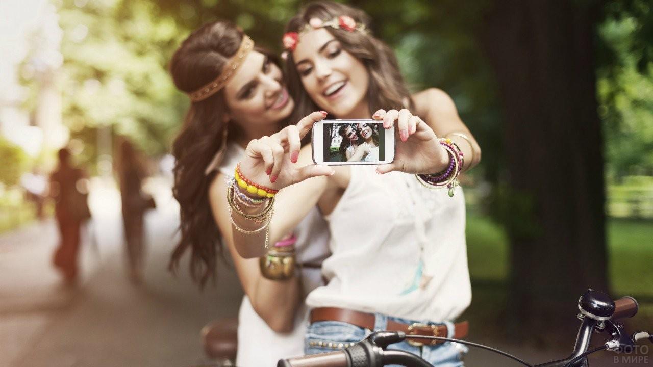 Две девушки на велосипеде делают селфи
