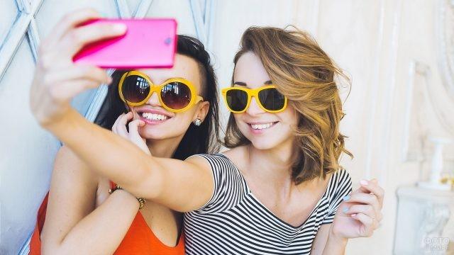 Две девушки в больших очках фотографируются