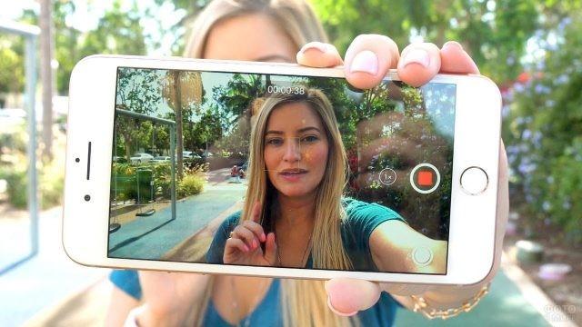 Изображение девушки на экране телефона