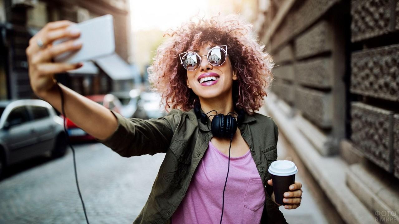 Кудрявая девушка фотографирует сама себя