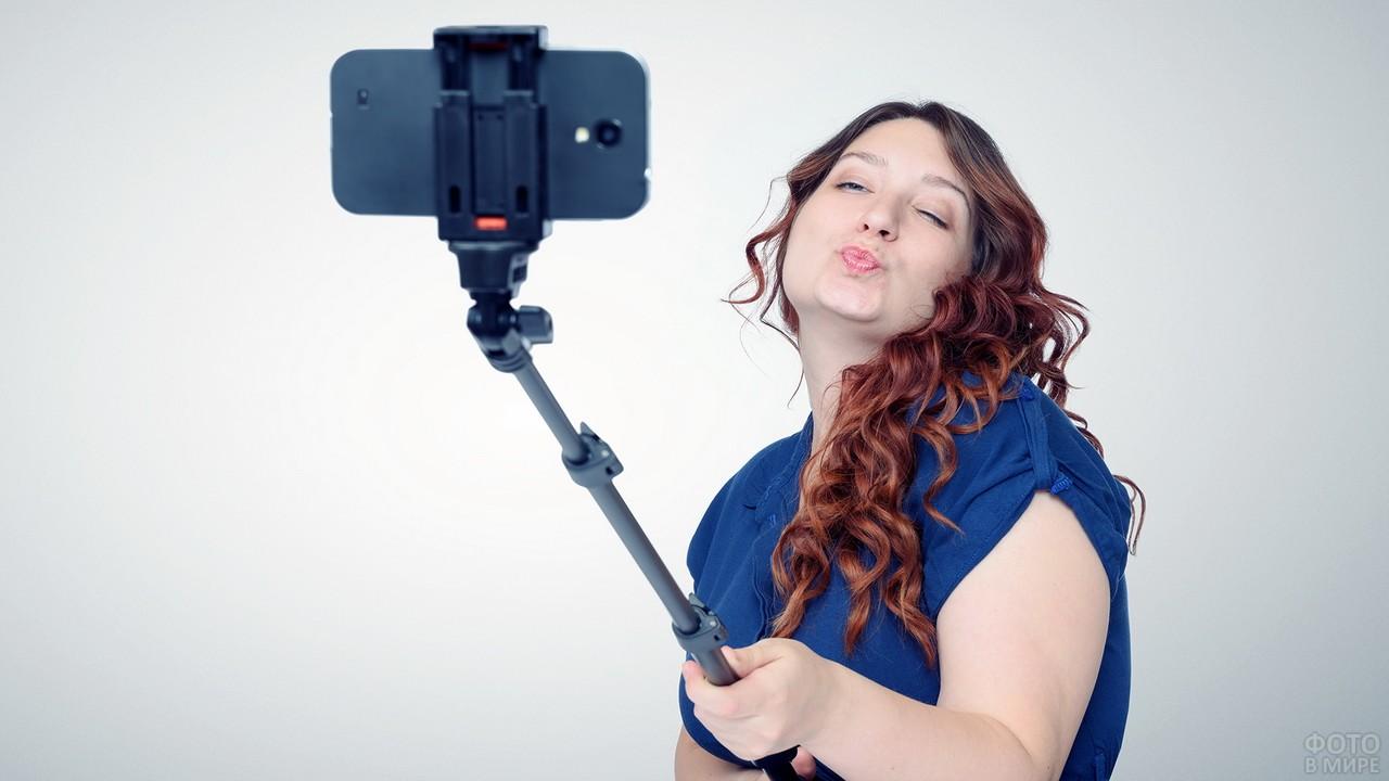 Пухленькая девушка делает фото на телефон