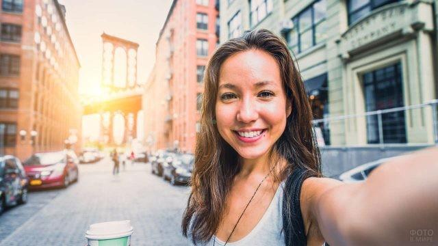 Счастливая девушка фотографируется на улице