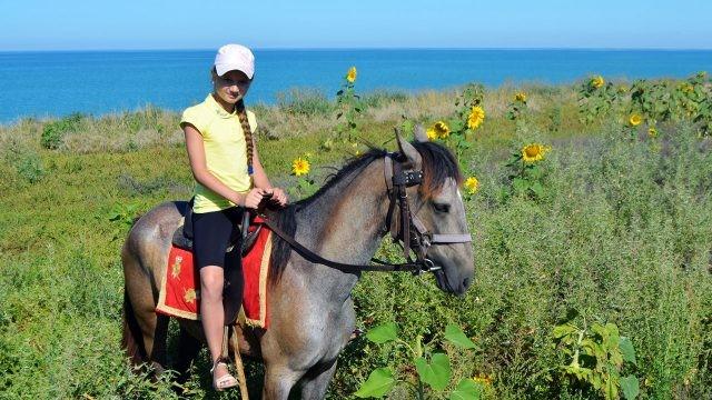 Девочка на конной прогулке по берегу моря