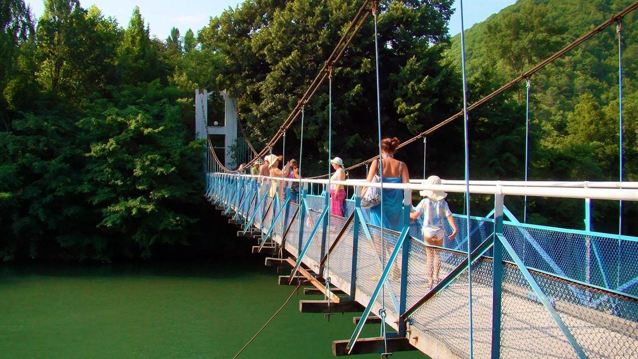 Туристы на мостике через реку Вулан