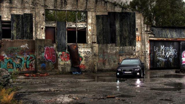 Чёрная ауди около заброшенного здания