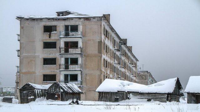 Деревянные постройки рядом с заброшенными многоэтажками зимой
