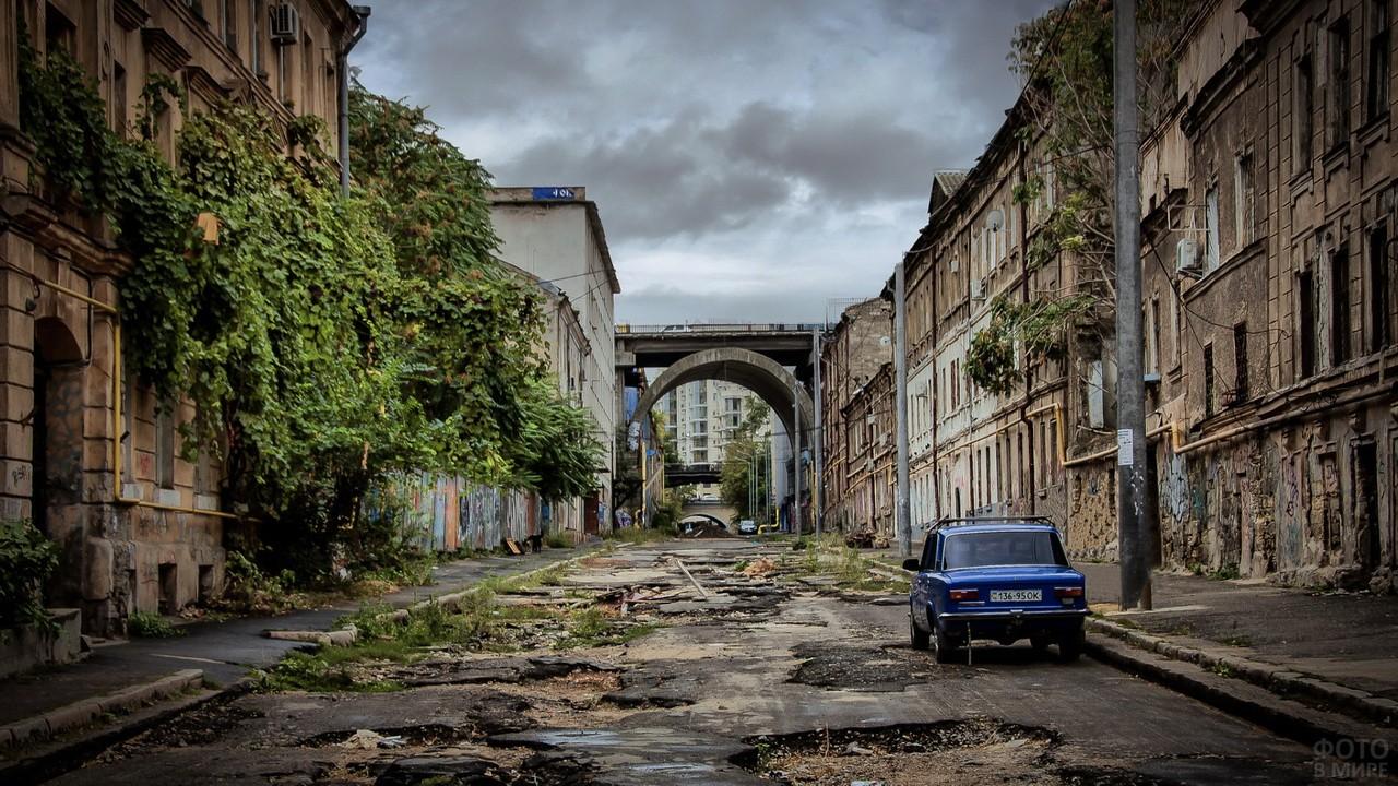 Синие Жигули на разбитой городской улице