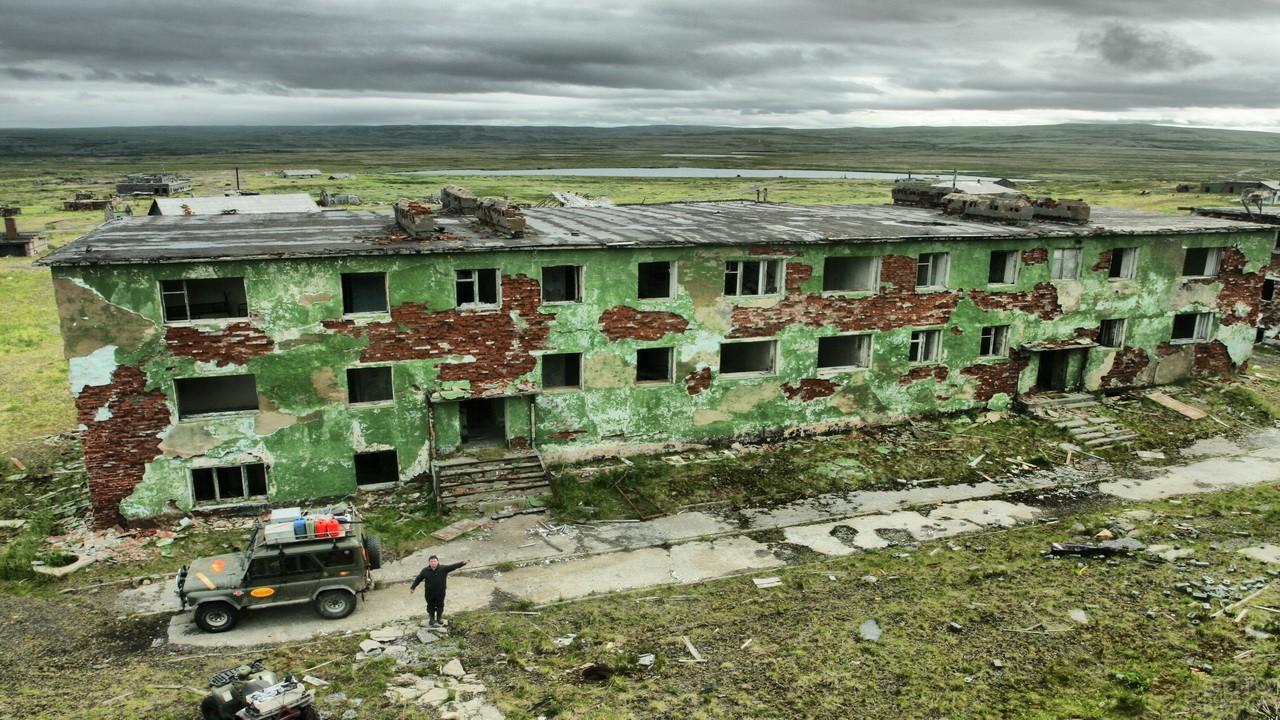 УАЗ и турист рядом с заброшенным зелёным домом