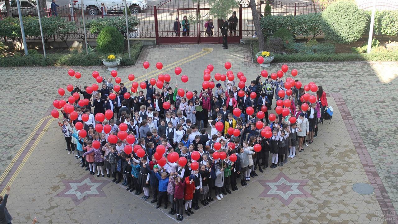 Дети построились во дворе для флешмоб-открытки в форме сердечка