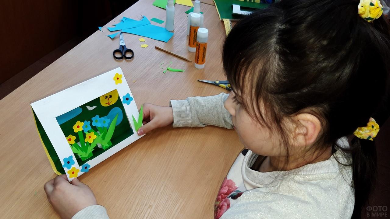 Девочка держит в руках самодельную объёмную открытку с цветами