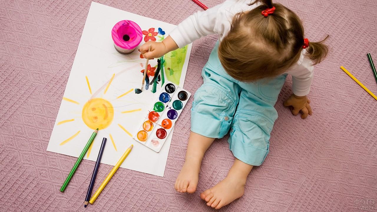 Девочка рисует солнышко и цветы