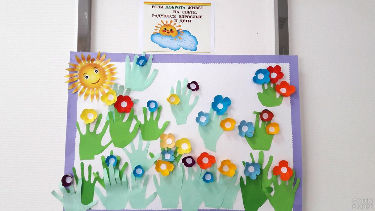 Ладошки с цветами из цветной бумаги на стенде в детском саду