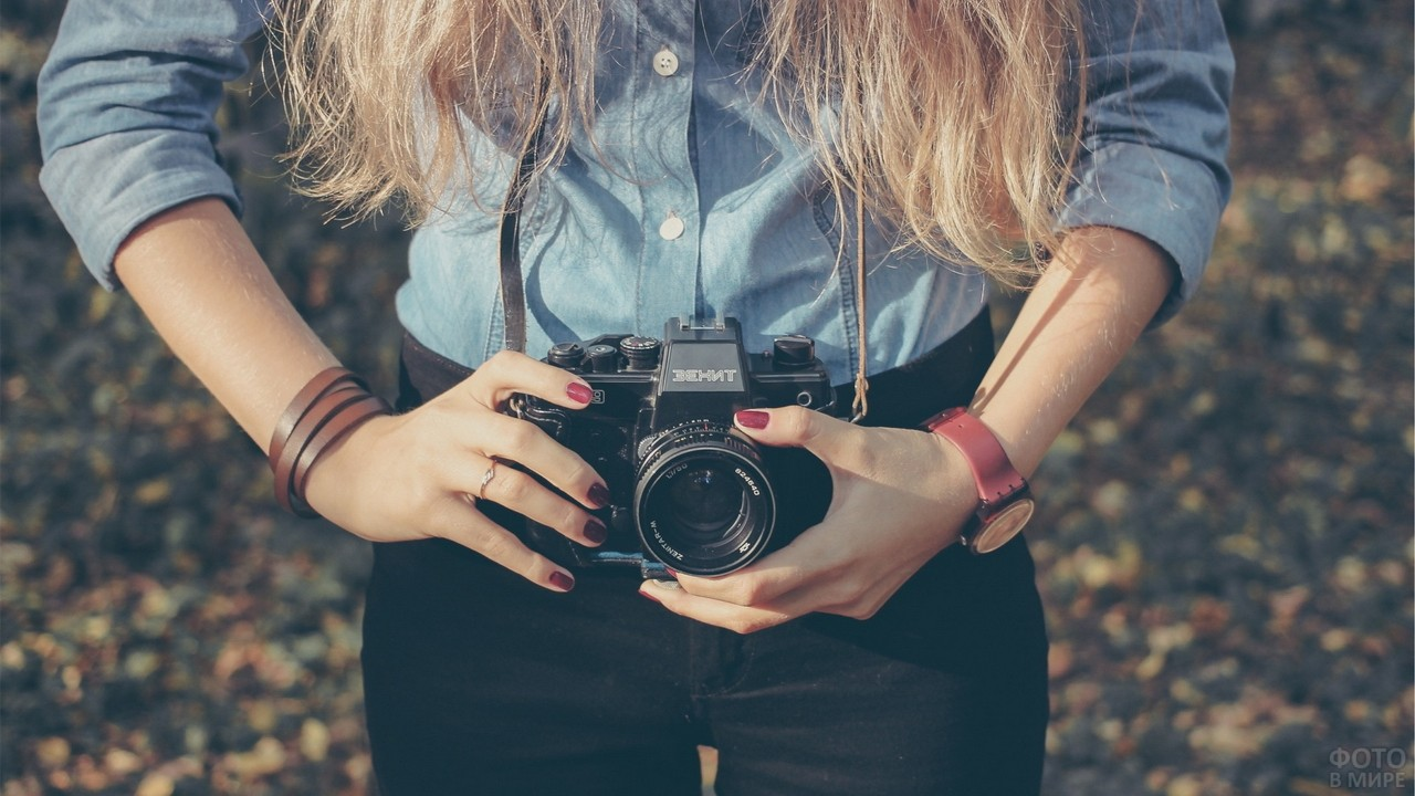Блондинка крутит объектив на фотоаппарате Зенит