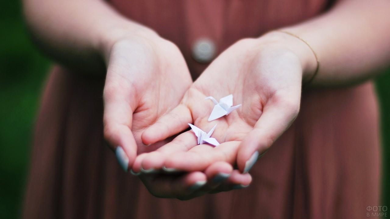 Бумажные журавлики в руках у девушки
