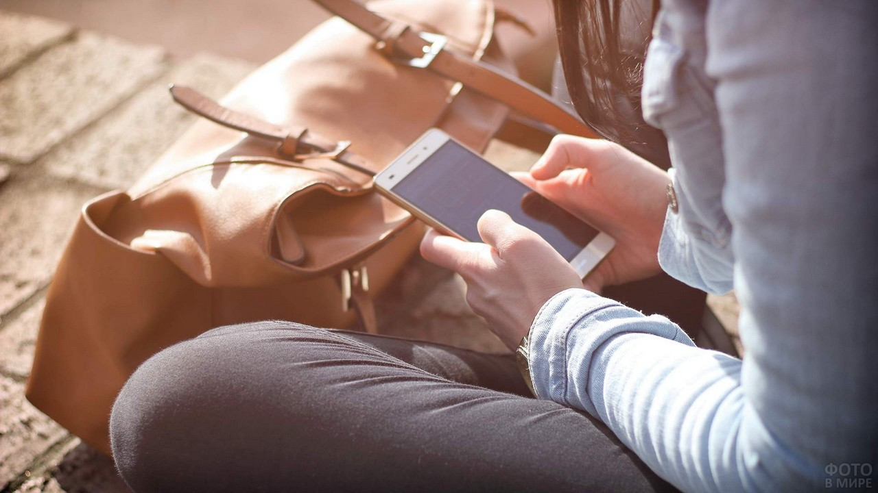 Девушка что-то набирает в телефоне