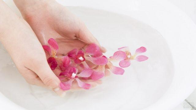 Девушка моет руки в ванночке с лепестками