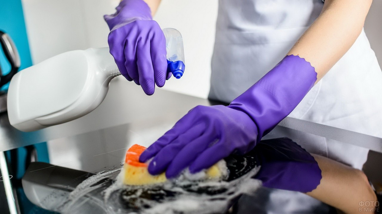 Девушка в перчатках чистит плиту спецсредством
