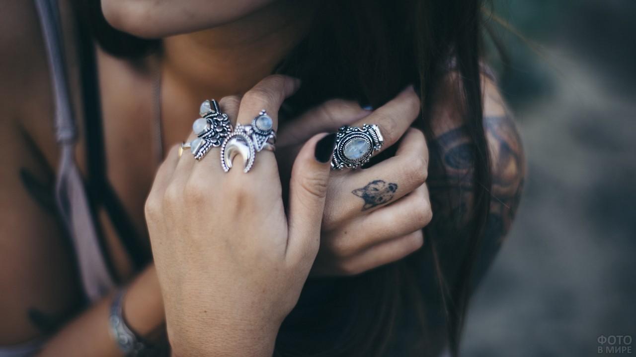 Кольца из белого металла на пальцах девушки