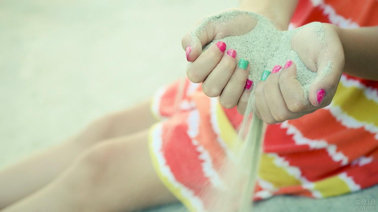 Песок сквозь пальцы с ярким маникюром
