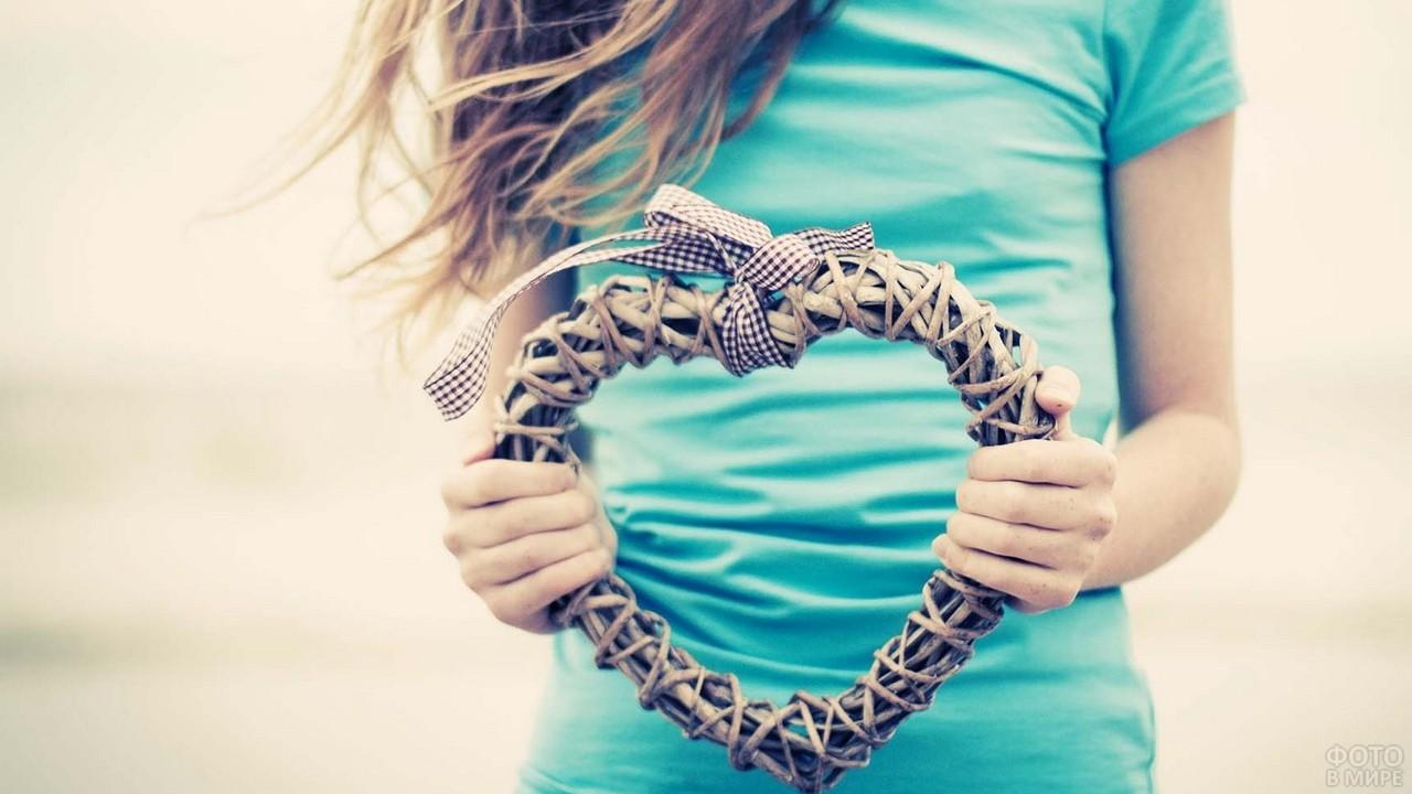 Плетёное сердце в руках у девушки