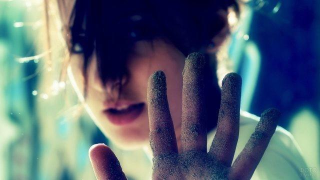 Рука девушки в песке