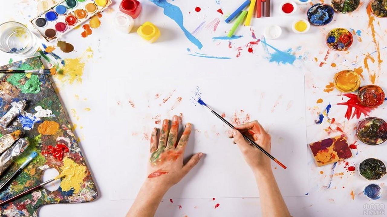 Руки девушки на белом листе среди красок и кистей