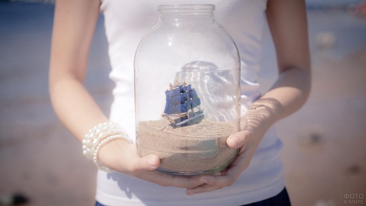 Руки с браслетом из бус держат банку с корабликом