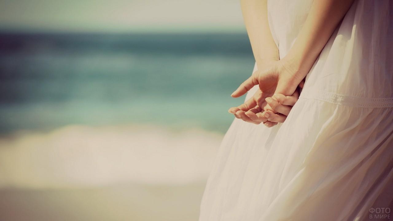 Руки за спиной на фоне моря
