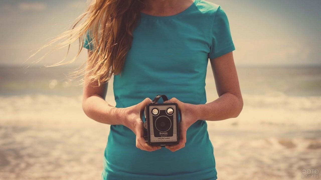 Старинный фотоаппарат в руках девушки