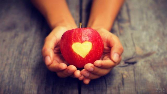 В руках у девушки яблоко с вырезанным сердцем
