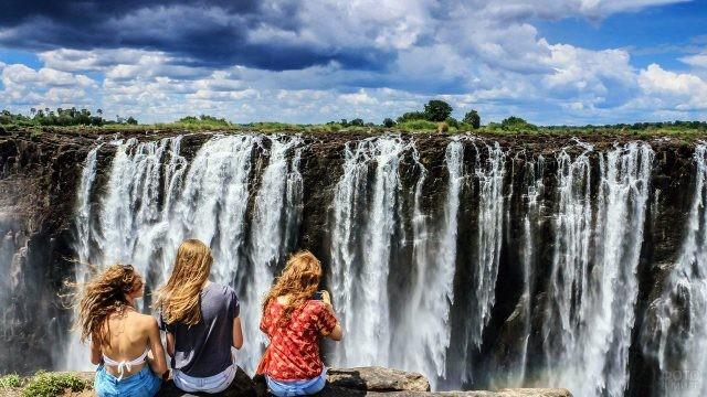 Девушки сидят на обрыве на фоне водопада Виктория