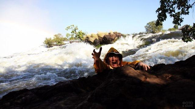 Турист кривляется на фоне водопада Виктория со стороны Замбии
